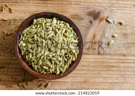 Fennel seeds in a small wooden bowl on an old wooden table. - stock photo