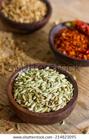 Fennel seeds in a small wooden bowl on an old wooden table. Other spices in the background. - stock photo
