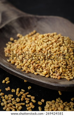 Fenugreek seeds on wooden spoon - stock photo
