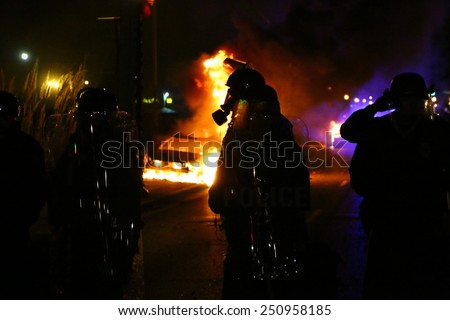 FERGUSON, MO - NOVEMBER 24, 2014: Silhouette of a police officer standing amid flames after riots broke out in Ferguson, Missouri on November 24, 2014. - stock photo