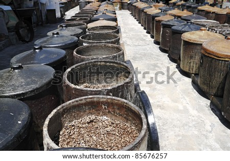 Fermenting soybean in rows of ferment pot at a traditional soya sauce factory in Kampung Malabar, Penang, Malaysia. - stock photo