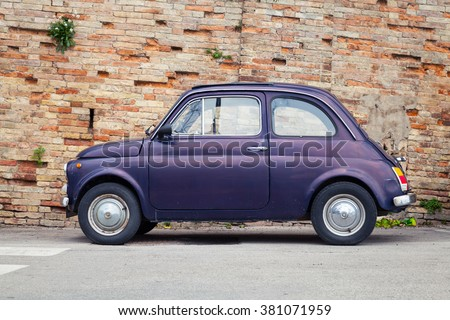 Fermo, Italy - February 11, 2016: Old Fiat Nuova 500 city car produced by the Italian manufacturer Fiat between 1957 and 1975 stands in a town, side view - stock photo
