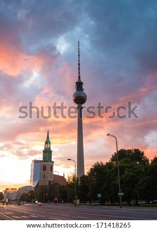 Fernsehturm television tower and dramatic sunlit sky at first light in the vibrant city of Berlin, Germany. - stock photo