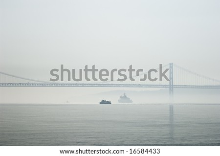 Ferries crossing the Tagus river near 25th April bridge in a foggy morning - stock photo