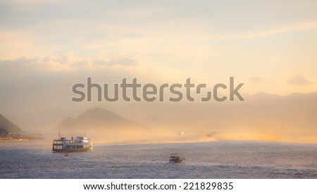 Ferries on the ocean at dusk - stock photo