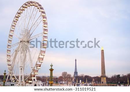 Ferries wheel in Paris at dusk. Eiffel Tower on the background.  - stock photo