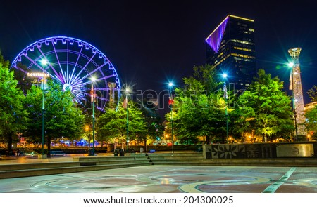 Ferris wheel and buildings seen from Olympic Centennial Park at night in Atlanta, Georgia. - stock photo