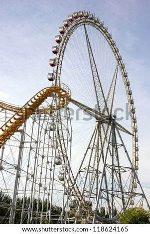 Ferris wheel and roller coaster at sunset. - stock photo