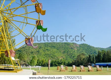 ferris wheel and target rang in park. - stock photo