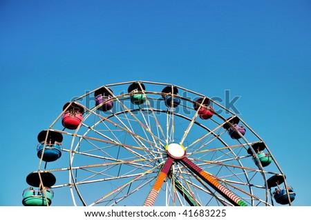 Ferris wheel at an amusement park against blue sky background - stock photo