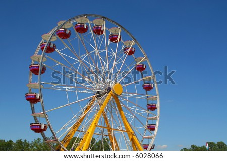 Ferris wheel at state fair set against clear blue sky background - stock photo