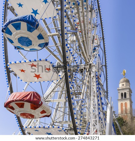 Ferris Wheel at the county fair with the sky in the background and a bell tower - stock photo