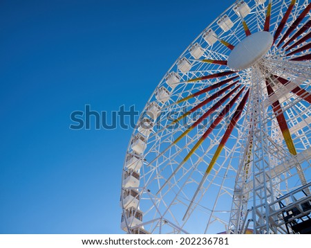 ferris wheel in a fairground against blue sky - stock photo
