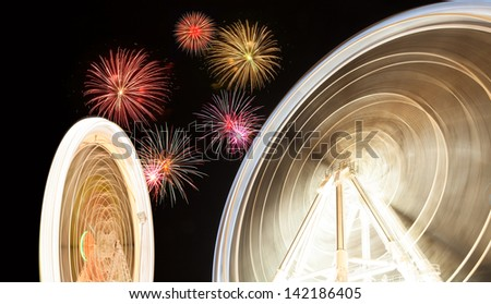 Ferris wheel in action in an amusement park at night, with fireworks in the sky - stock photo