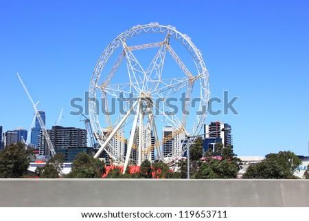 Ferris wheel in city setting against blue sky - stock photo