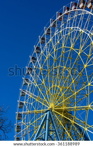 Ferris wheel in Tbilisi on bright blue sky background