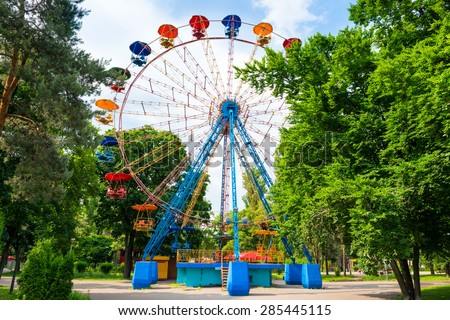 Ferris wheel in the green park over blue sky with clouds - stock photo