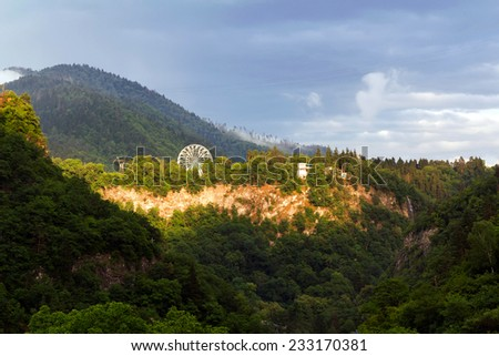 Ferris wheel in the mountains above the abyss - stock photo