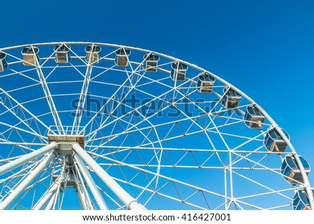 Ferris wheel on the background of clear blue sky on a sunny day