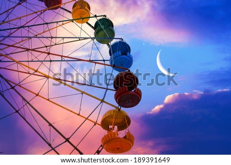 Ferris wheel on the moon colorful sky background - stock photo