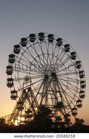 Ferris wheel silhouetted against the darkening sky as the sun sets over the Pushkar fair in Rajasthan, India