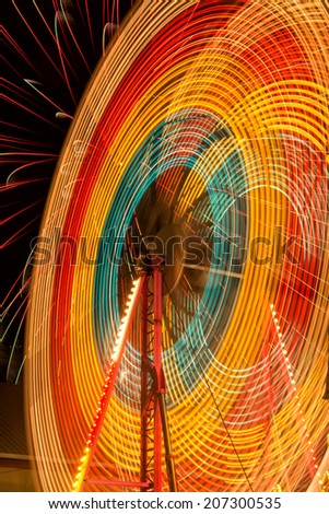 Ferris Wheel spins in front of a firework show - stock photo