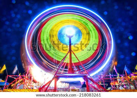 Ferris wheel taken at night using a long exposure to capture the motion of the ride.  A fine mist on the lens due to weather refracts the lights into dramatic highlights in the background. - stock photo