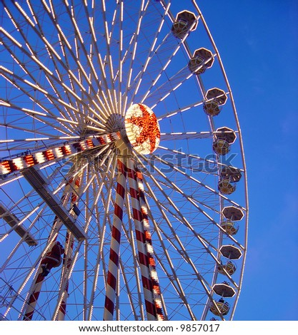 Ferris wheel with lights around against a blue sky