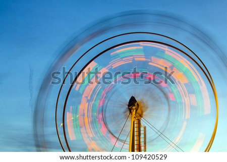 Ferris wheel with motion blurred lights - stock photo