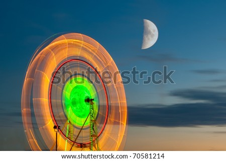 Ferris Wheel with the moon. Slow shutter image of a moving ferris wheel at the North Carolina State Fair. Image was taken at dusk showing the lights on the ferris wheel with moon in the background. - stock photo