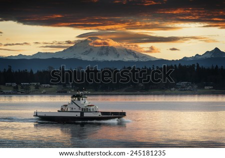 "Ferry and Mt. Baker. The ferryboat ""Whatcom Chief"" sails from Gooseberry Point to Lummi Island across Hales Pass in the San Juan Islands of Puget Sound. Mt. Baker is seen in the background at sunrise. - stock photo"
