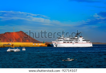Ferry boat approaches pier at Corralejo harbor; Fuerteventura, Canary islands, Spain - stock photo