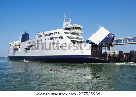 ferry boat at pier loading cargo from port and passenger boarding and from terminal  - stock photo