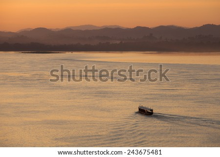 Ferry boat in Mekong River with the light of sunset, North Thailand - stock photo