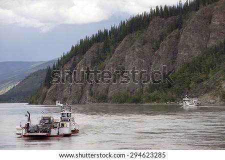 Ferry boat on Yukon River, Dawson City, Yukon - stock photo