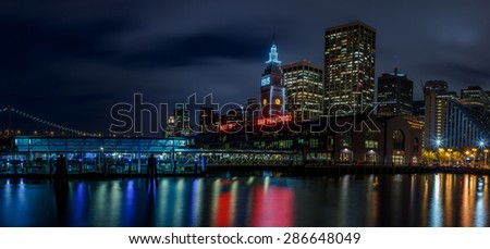 Ferry Building and Bay Bridge illuminated at night in San Francisco, California, USA