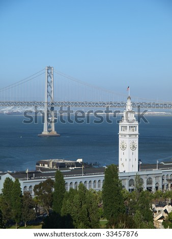 Ferry Building & Bay Bridge is steeped in golden sunshine. - stock photo