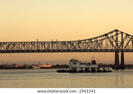 Ferry crossing Mississippi rover at sunset in New Orleans - stock photo