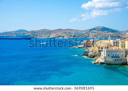 Ferry entering the port of Syros island in Greece during summer. Neoclassical buildings on the foreground.