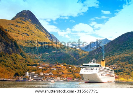 Ferry in Geiranger. bay in the Norwegian mountains. Gold autumn - stock photo