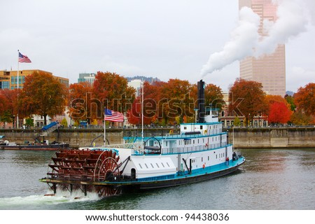 Ferry or steam boat in Portland on Willamette river under steam with two American flags on an overcast day - stock photo