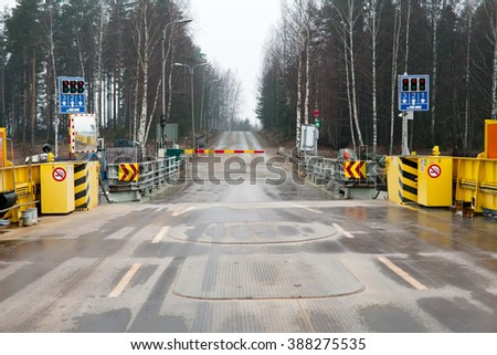 ferry pier with closed barrier to straight highway road view - stock photo