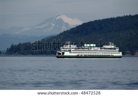 Ferry sailing through Puget sound with Mt. Baker on a background
