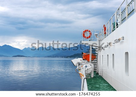 Ferry ship sailing in still water of a fjord arriving in a destination port. View from the deck of a ferry boat - stock photo