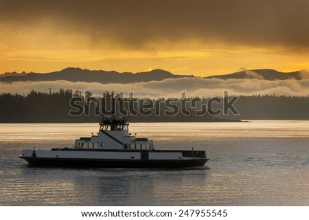 Ferryboat and the Cascade Mountains. A ferryboat makes the crossing to its island destination in the Puget Sound area of western Washington state. The Cascades mountains are seen in the background. - stock photo