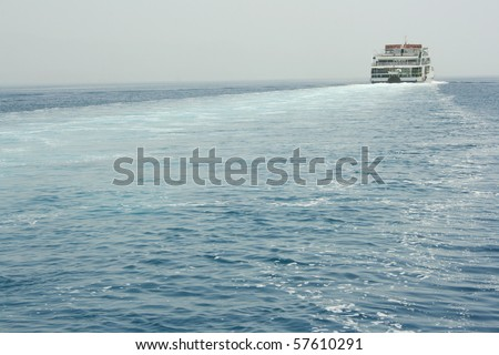 Ferryboat is moving across sea and makes waves behind his aft (photo has lot of copy-space). Focus on ferry