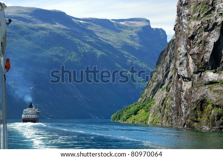 Ferryboat is sailing by the Geirangerfjord. Large ship is navigated along the sheer mountain cliffs.
