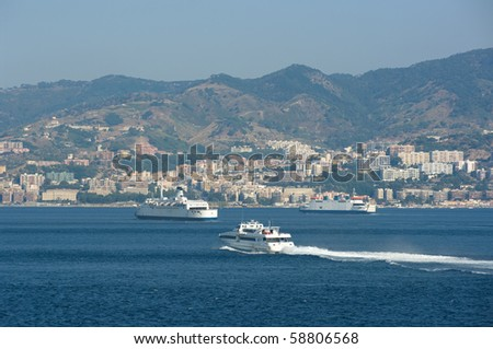 ferryboats in the canal of  Messina on the background the city's skyline - stock photo