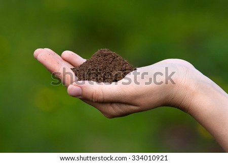 fertile soil in hand of women - stock photo