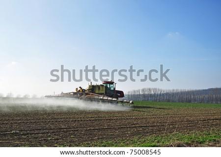 Fertilization agriculture, fertilizer application by field mechanization - stock photo